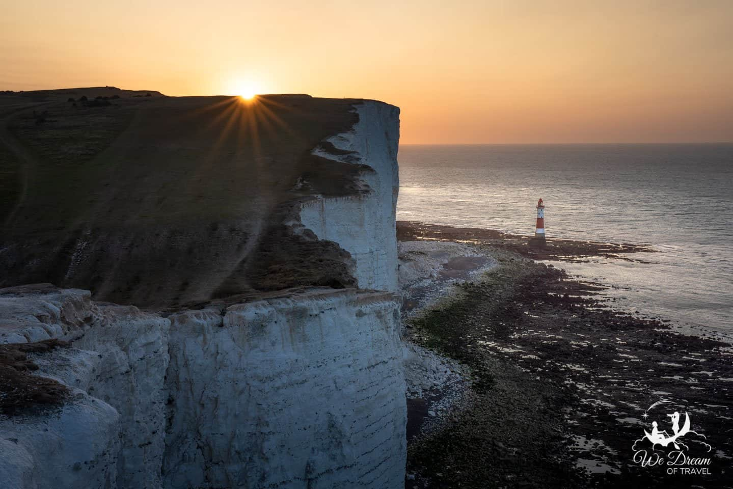 The rising sun peaks over the white cliffs at the Beachy Head Lighthouse at sunrise.