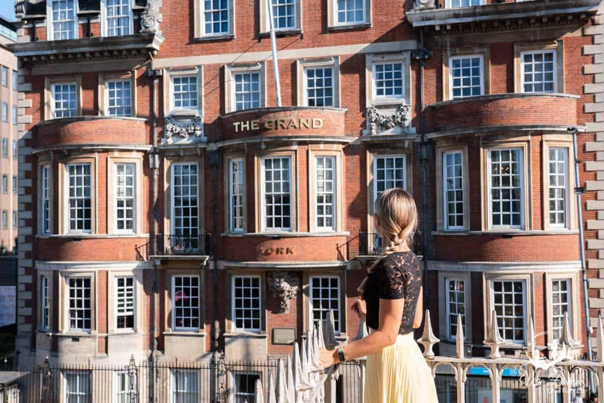 A girl looking back at The Grand Hotel from the York city walls.