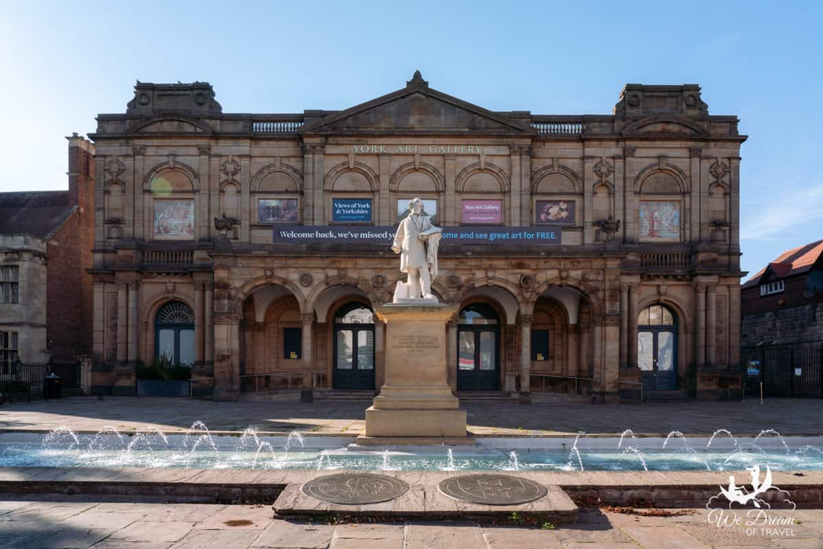 The front of York Art Gallery with water fountain and statue in front.