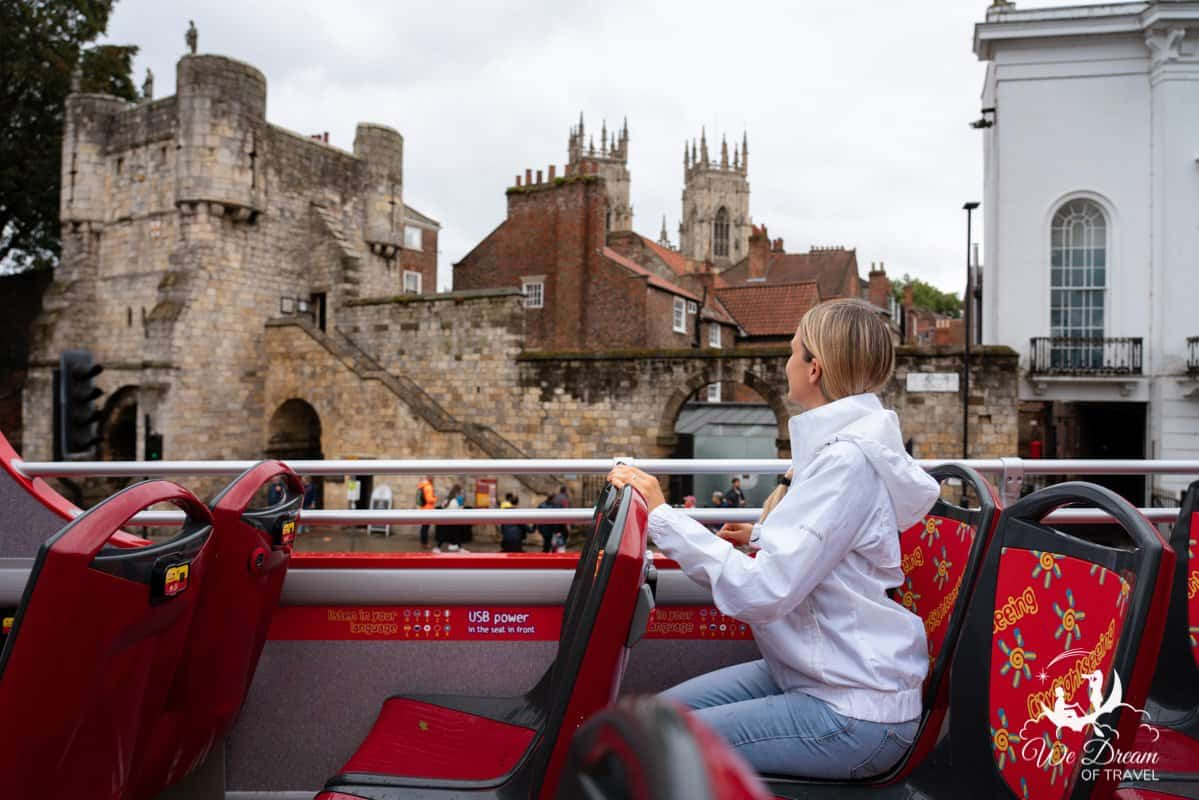A girl sat at the top of the York City Sightseeing bus in front of Bootham Bar - one of the best things to do in York.
