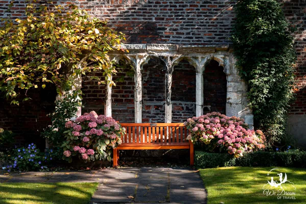 A bench surrounded by pink flowers set against stone ruins in the gardens of Merchant Adventurers Hall York