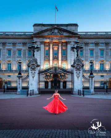 A girl in a ball gown in front of Buckingham Palace at dusk