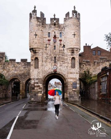 A girl with a rainbow coloured umbrella in front of Micklegate Bar on a grey, rainy day in York!