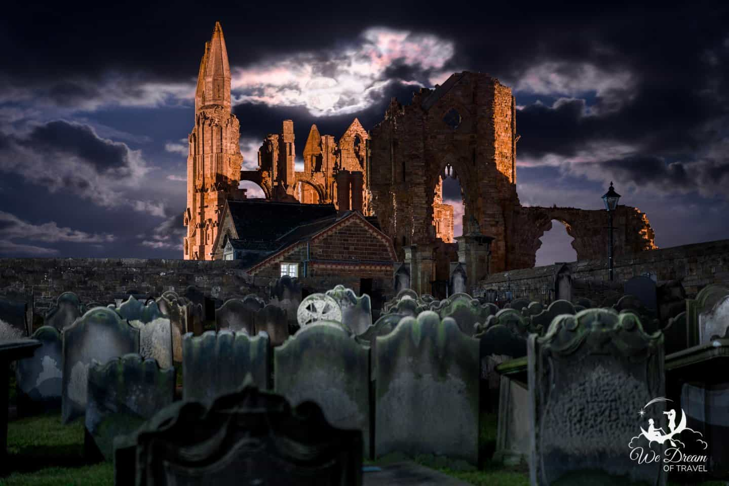 Night photography of Whitby Abbey and St Mary's Church graveyard under a full moon create a spooky scene.