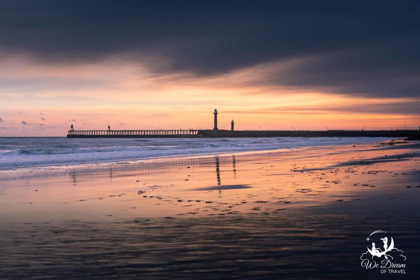 A vibrant sunrise at Whitby Beach looking back towards the piers.