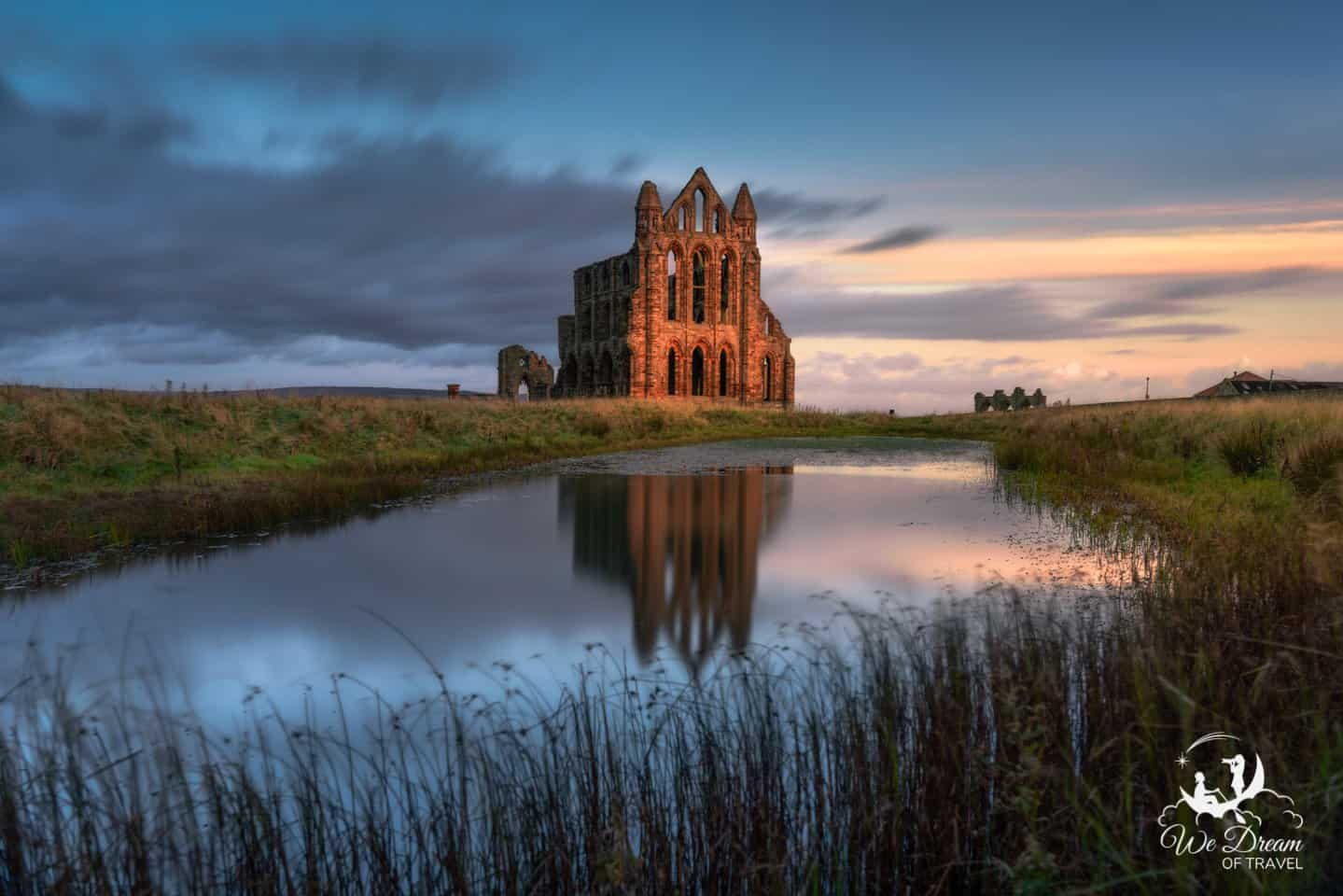 Long exposure photography of Whitby Abbey reflection in the lake at sunrise - one of the most famous things to do in Whitby.