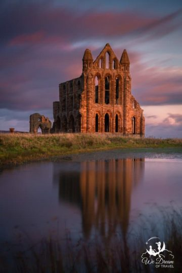 Whitby Abbey reflected in the lake at sunrise - one of the must see attractions in Whitby