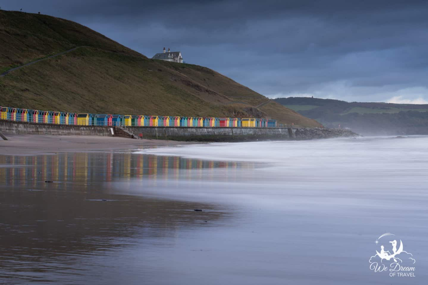 Long exposure photograph of Whitby Sands beach with colourful beach huts lining the seafront.
