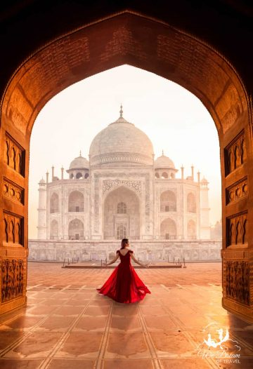 A girl in a red dress and the Taj Mahal framed by a door way at sunrise.