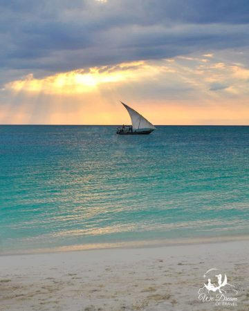 A traditional dhow sails just off the shore of Zanzibar at sunset.