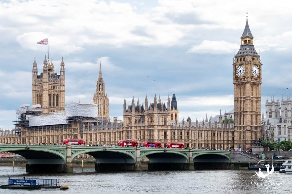 Westminster Bridge with iconic red double decker buses, in front of Big Ben and Houses of Parliament, some of the most famous landmarks in London.