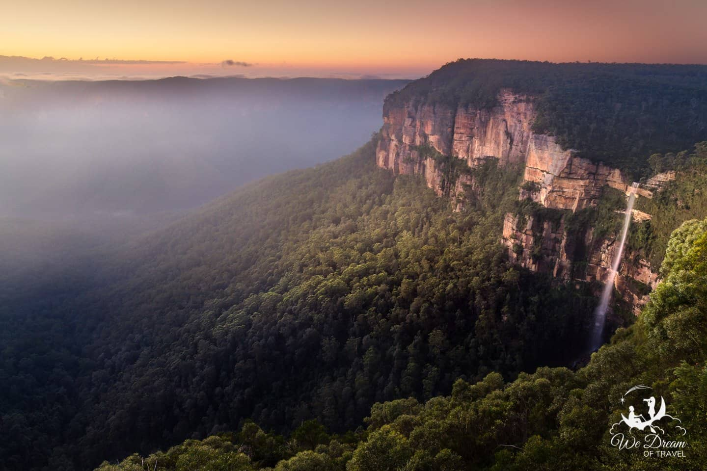 A large waterfall tumbles off the rock wall at sunrise while a eucalyptus mist gathers at Blue Mountains National Park in Australia.