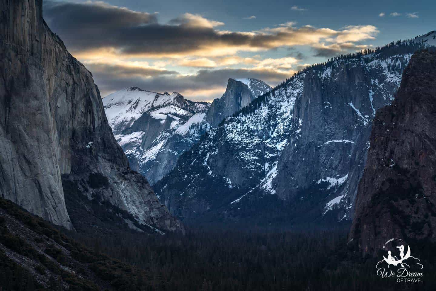 Gold-tinted clouds frame Half Dome at sunrise.