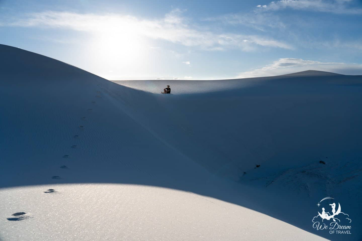 Footprints in the glittering sand leading to a man sitting in the afternoon sun on the gypsum sand dunes at White Sands NM.