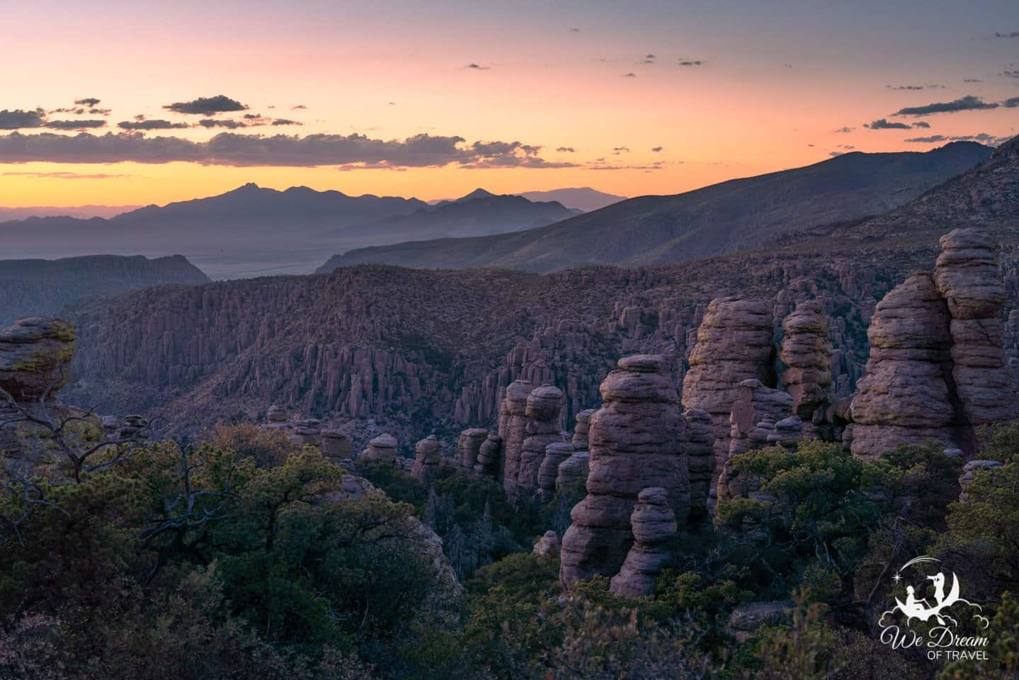 Sunset lights up the sky with oranges and pinks above the rocks at Chiracahua