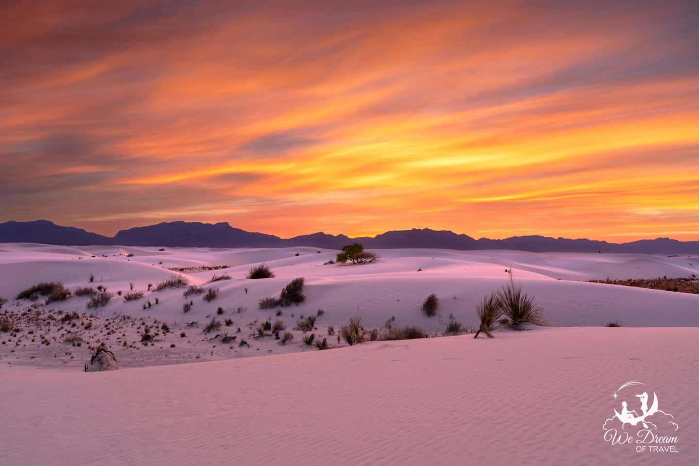 A sky fire sunset reflects off the sand dunes, turning the entire scene pink and orange at White Sands National Park NM.
