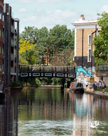 A bridge over Regent's Canal with a parked narrowboat and street art along the wall