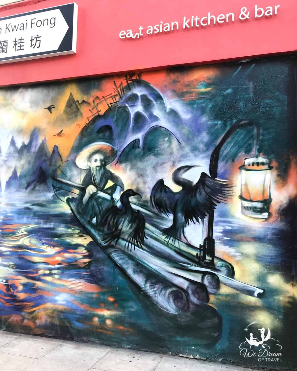Camden street art of an Asian man on a raft with a lantern and fishing birds on Hartland Road