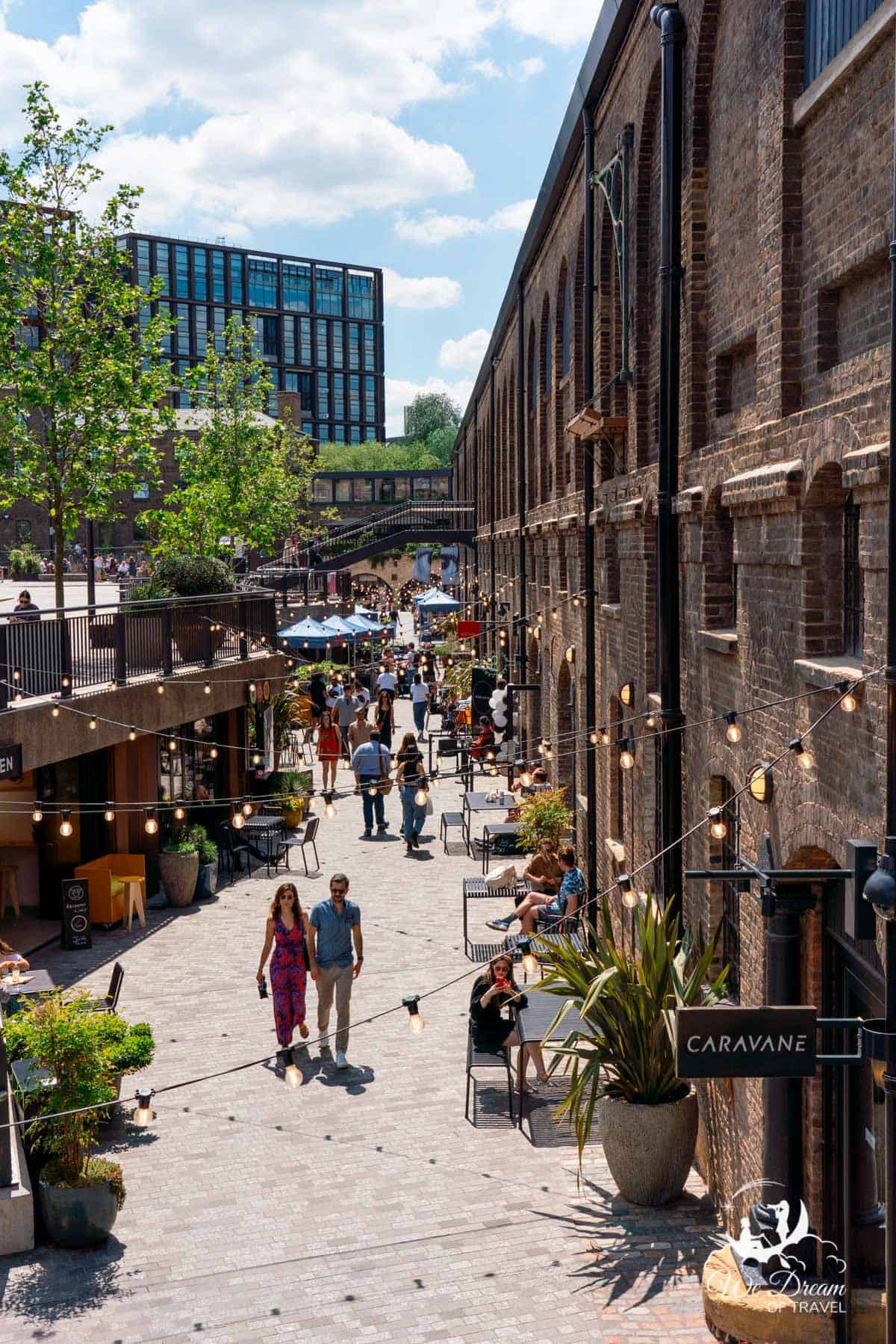 Shops and restaurants line a walkway with overhanging lights at Coal's Drop Yard, King's Cross, London