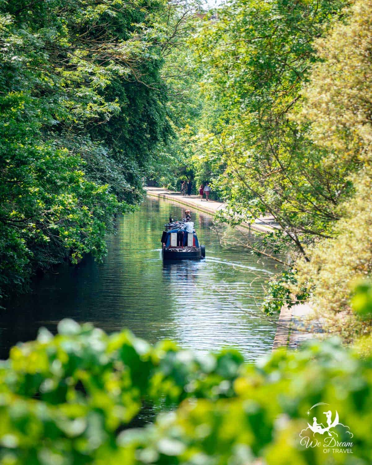 A narrow boat on the Regent's Canal framed by greenery