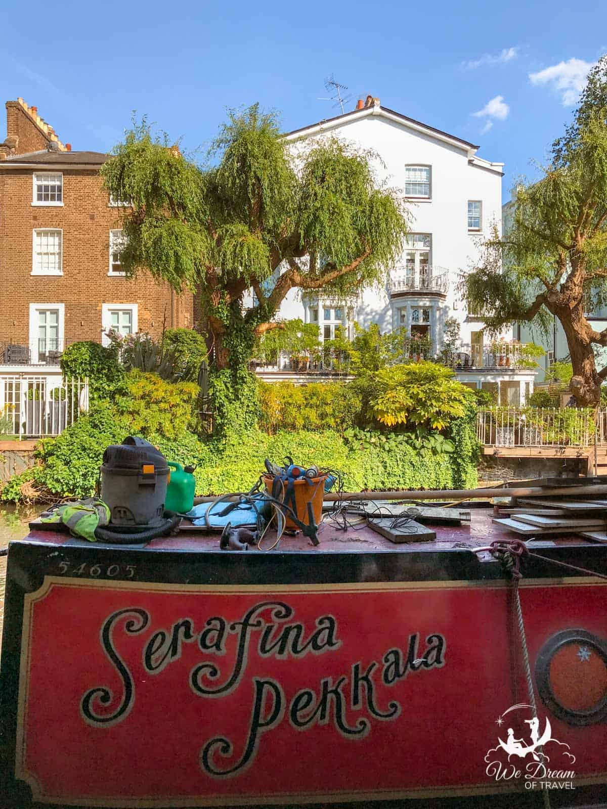 A houseboat on the Regent's Canal with a beautiful house behind it