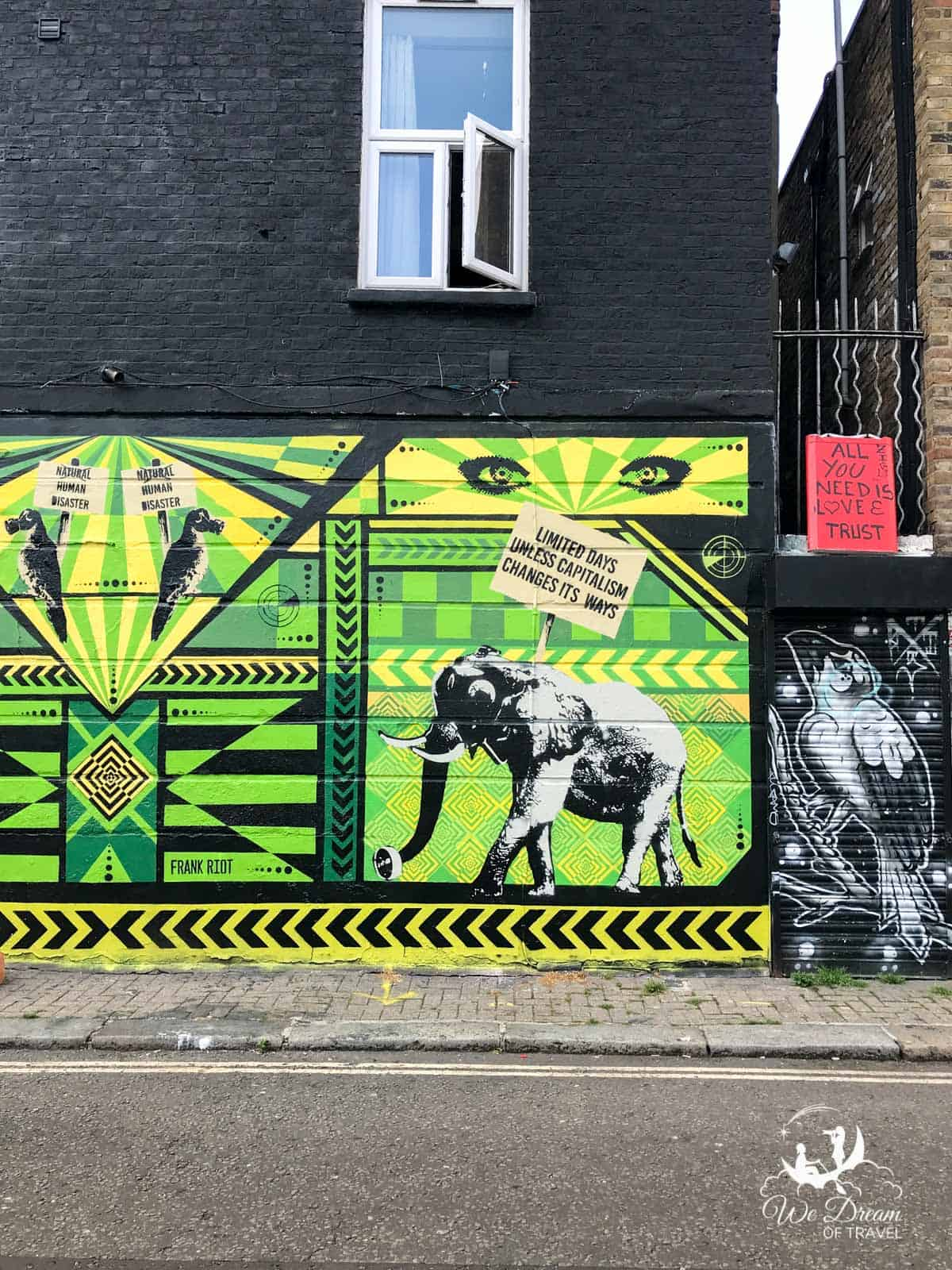 Bright green street art mural featuring an elephant holding a sign and geometric shapes on Stucley Place, Camden