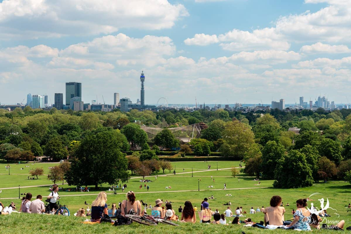 People enjoying a picnic in the sunshine atop Primrose Hill, looking out over the London skyline.