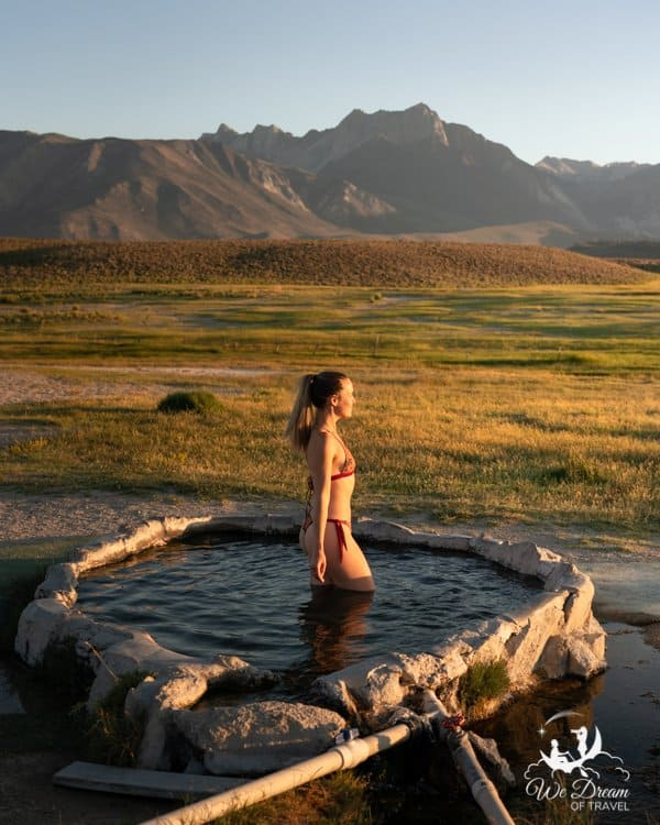A girl standing in Hilltop Hot Spring Mammoth Lakes at golden hour