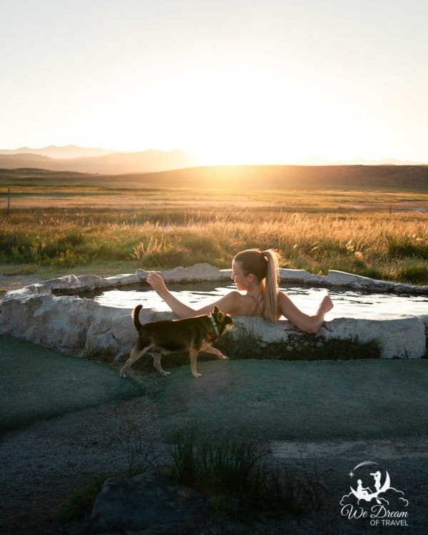 A girl sat in Hilltop Hot Springs at sunset with a dog walking by