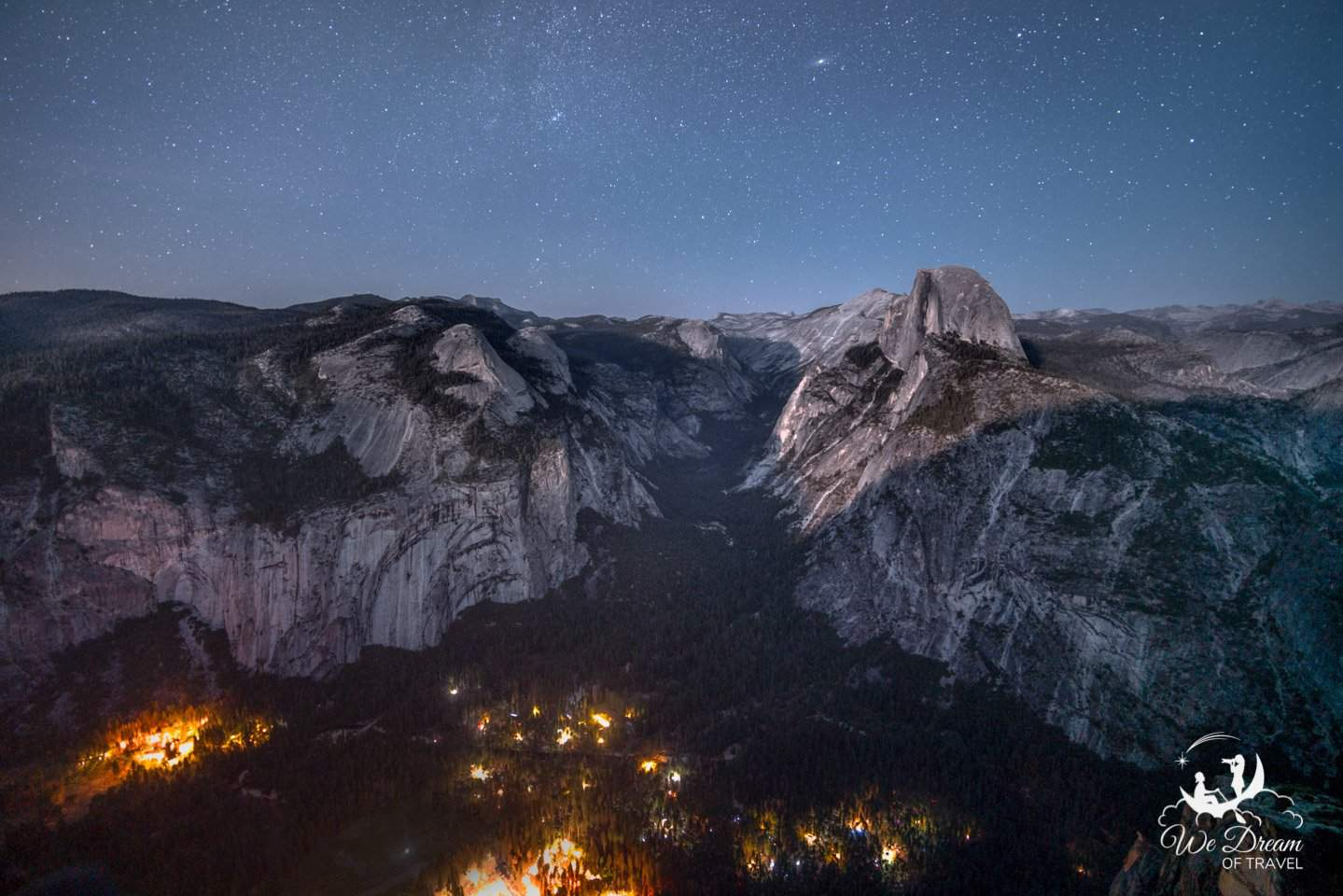 The lights from Yosemite Village illuminate the valley floor while the stars dance overhead at Glacier Point.