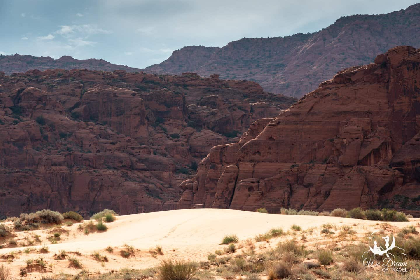 Sand dunes against a background of red rock in Snow Canyon.
