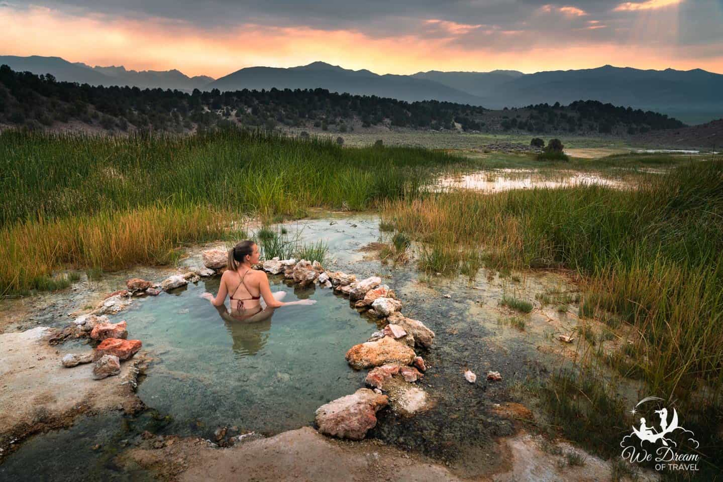 A girl sat in a shallow secret hot spring at sunset at Travertine Hot Springs