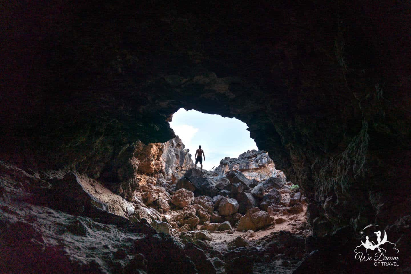 A man standing, silhouetted at the entrance of a lava tube in Snow Canyon State Park