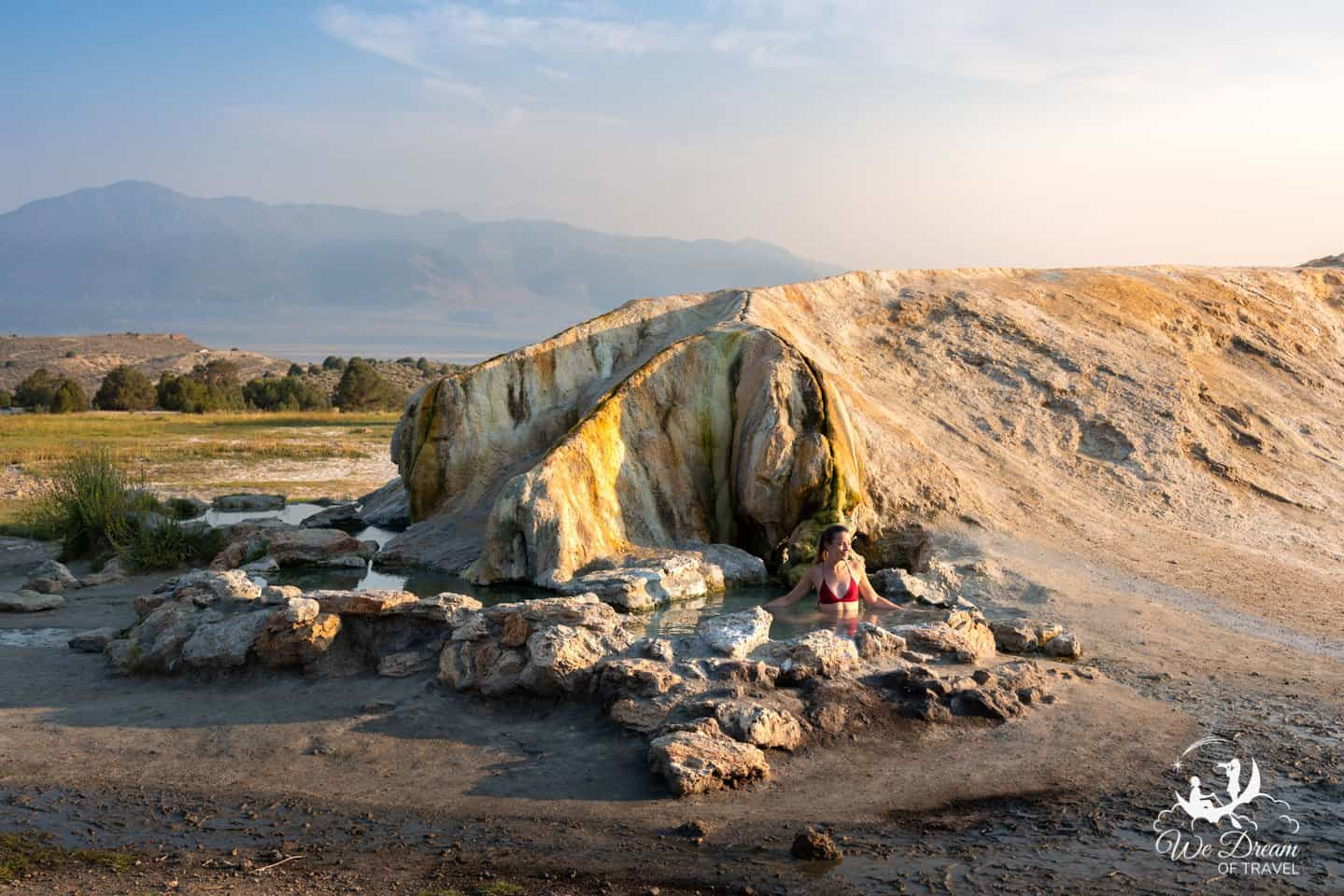 A girl enjoying Travertine Hot Springs main pools at sunrise with mountains in the background.