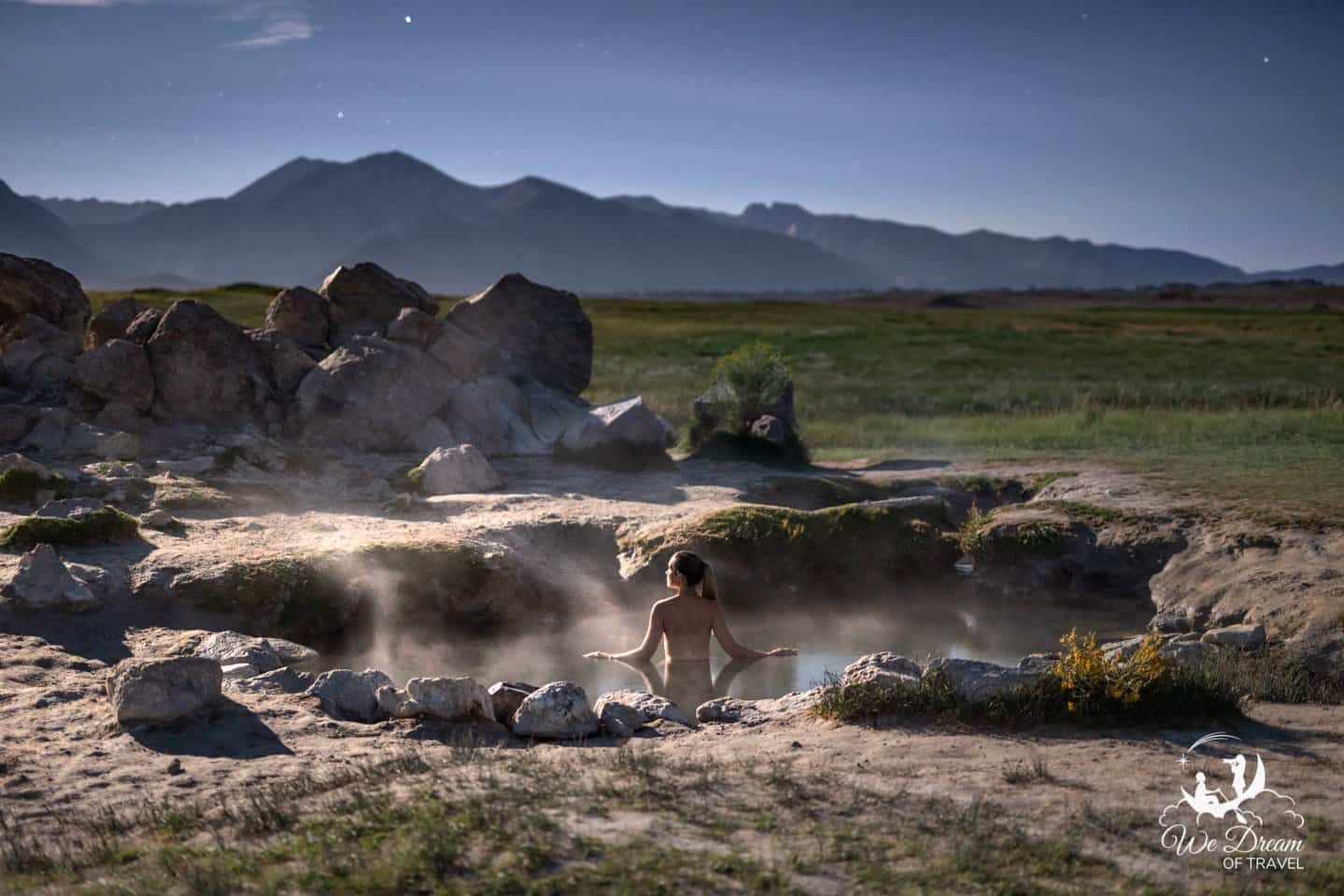 A girl soaks under moonlight at Wild Willys hot spring in Mammoth Lakes at night.